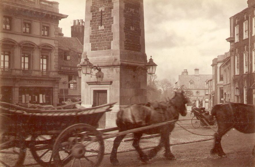 Two cart horses pulling a cart in front of the Clock Tower in the Market Place at Rugby.  The lamps on the tower were fixed in 1889.  Boughton House is on the extreme right, the ground floor of which was converted into a clothiers shop in 1901.  1900 |  IMAGE LOCATION: (Rugby Library)