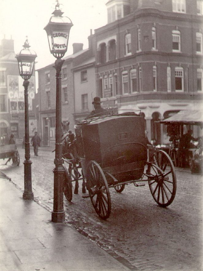 A horse drawn cab waiting in Rugby Market Place.  1894 |  IMAGE LOCATION: (Rugby Library)