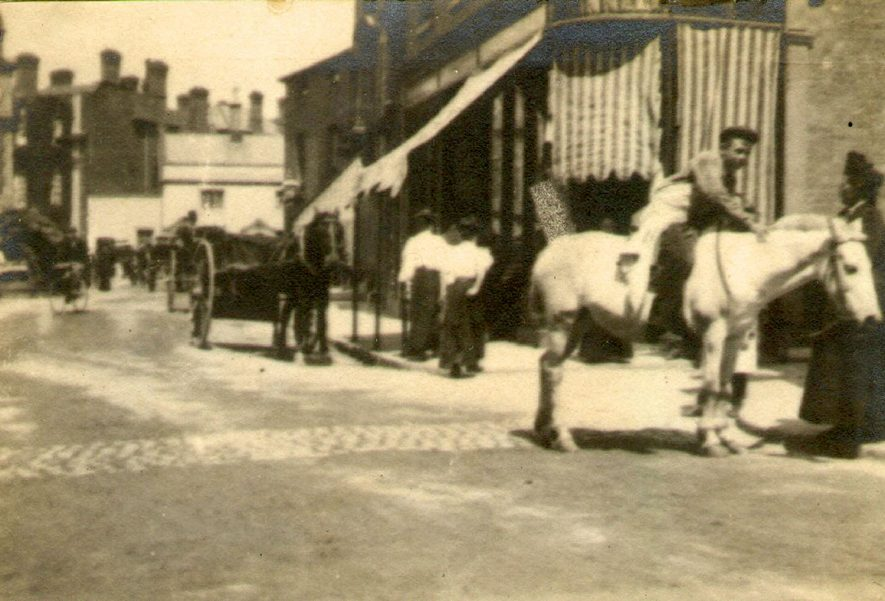 Market Place in 1897.  The shop with the blinds was McKinnell's, No 4 Market Place.  1897 [This shop is thought to be at 26/27 Sheep Street. A descendant of the family has stated that there is no reference to them ever having been in Market Place] |  IMAGE LOCATION: (Rugby Library)