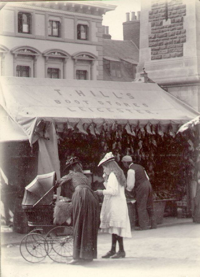 Market stall adjacent to the clock tower in Market Place, Rugby.  c. 1900 |  IMAGE LOCATION: (Rugby Library) IMAGE DATE: (c.1900)
