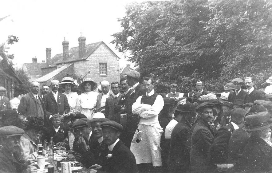 Group of people sitting round trestle tables at the coronation in 1911. |  IMAGE LOCATION: (Warwickshire County Record Office)