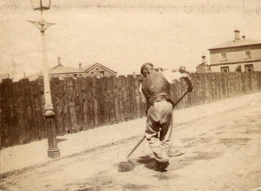 Man sweeping the road. Railway Terrace, Rugby, which was laid out as a private road by the Railway Company and lined with sleepers in 1840.  Plans for Railway Villas [one of which can be seen on the right] were passed in 1852.  This photograph was therefore taken after 1852. |  IMAGE LOCATION: (Rugby Library)