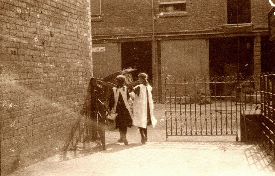 Two young girls walking through some wrought iron gates into St Matthew's Street.  1900 |  IMAGE LOCATION: (Rugby Library)