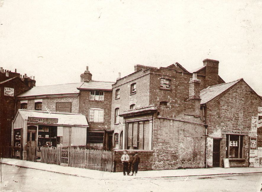Road junction showing [Albert] Frost's Printing Offices, 1, Warwick Road; A. Hall's Basket Maker, 38 Dunchurch Road, (also had 2 Sheep Street); W[illiam] Daynes Photographer, (in 1884 he had moved to 92 Railway Terrace). 1880 |  IMAGE LOCATION: (Rugby Library)
