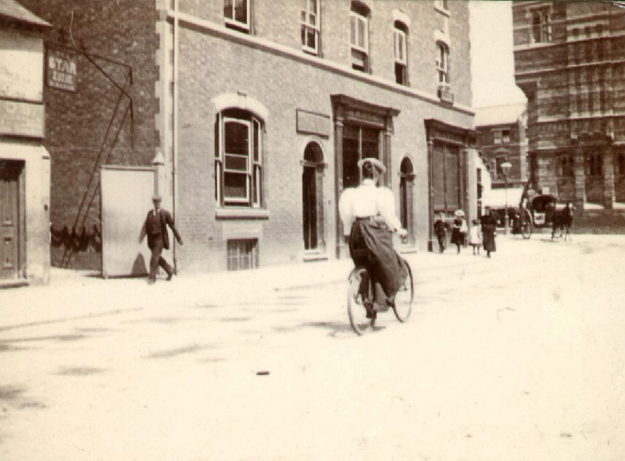A lady cyclist riding in Warwick Street, Rugby.  1900 |  IMAGE LOCATION: (Rugby Library)