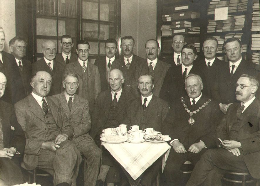 The re-opening of Rugby Borough Museum, showing (from left to right, back to front) Councillor N D Johnstone, Councillor G James, Councillor H Lupton Reddish, Mr T L Duffy (Assistant Town Clerk), Mr F G B Hutchings (Librarian), Councillor T A Lord, Councillor S P Marsh, Councillor J W Darby, Mr T Bartlett (Sanitary Inspector), Mr M A Stacey (Assistant Borough Treasurer), Mr C V Johnson (Deputy Electrical Engineer), Alderman C W Browning, Mr A White (Library Committee), Alderman J Tallon, Mr W A D Rudge (Library Committee), Mr E R Briggs (Library Committee), Alderman R H Myers (Chairman of Library Committee), Alderman R S Hudson (Mayor), Alderman J T Fleet.  1936 |  IMAGE LOCATION: (Rugby Library) PEOPLE IN PHOTO: White, Mr A, White as a surname, Tallon, Alderman J, Tallon as a surname, Stacey, Mr M A, Stacey as a surname, Rudge, Mr W A D, Rudge as a surname, Myers, Alderman R H, Myers as a surname, Marsh, S P, Marsh as a surname, Lupton Reddish, H, Lupton Reddish as a surname, Lord, T A, Lord as a surname, Johnstone, N D, Johnstone as a surname, Johnson, Mr C V, Johnson as a surname, James, G, James as a surname, Hutchings, Mr F G B, Hutchings as a surname, Hudson, Alderman R S, Hudson as a surname, Fleet, Alderman J T, Fleet as a surname, Duffy, Mr T L, Duffy as a surname, Darby, J W, Darby as a surname, Browning, Alderman C W, Browning as a surname, Briggs, E R, Briggs as a surname, Bartlett, Mr T, Bartlett as a surname