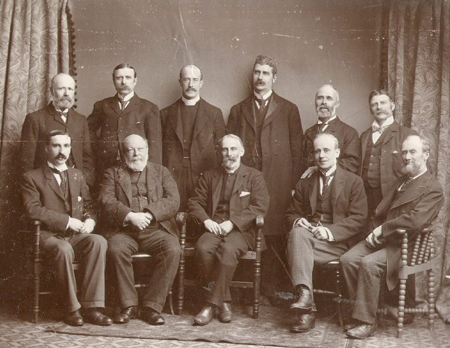 Group of members of St Matthew's Church Voluntary Council in 1901, Rugby. From back left - E T Fell, A G Salter, Rev. H Bancroft, T Duke, H Quilley, H Wykes. From front left - R H Myers, D Buchanan, Rev. A H Barker, W J Fell, A Harris. |  IMAGE LOCATION: (Rugby Library) PEOPLE IN PHOTO: Wykes, H, Salter, A G, Quilley, H, Myers, R H, Harriss, A, Fell, W J, Fell, E T, Duke, T, Buchanan, D, Barker, Revd H A, Bancroft, Revd H