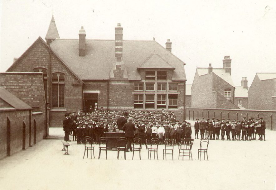 Pupils and staff in St Andrew's school playground for prize giving, Rugby.  School building in background.  Donated by Mr J. Twells.  1906 |  IMAGE LOCATION: (Rugby Library)