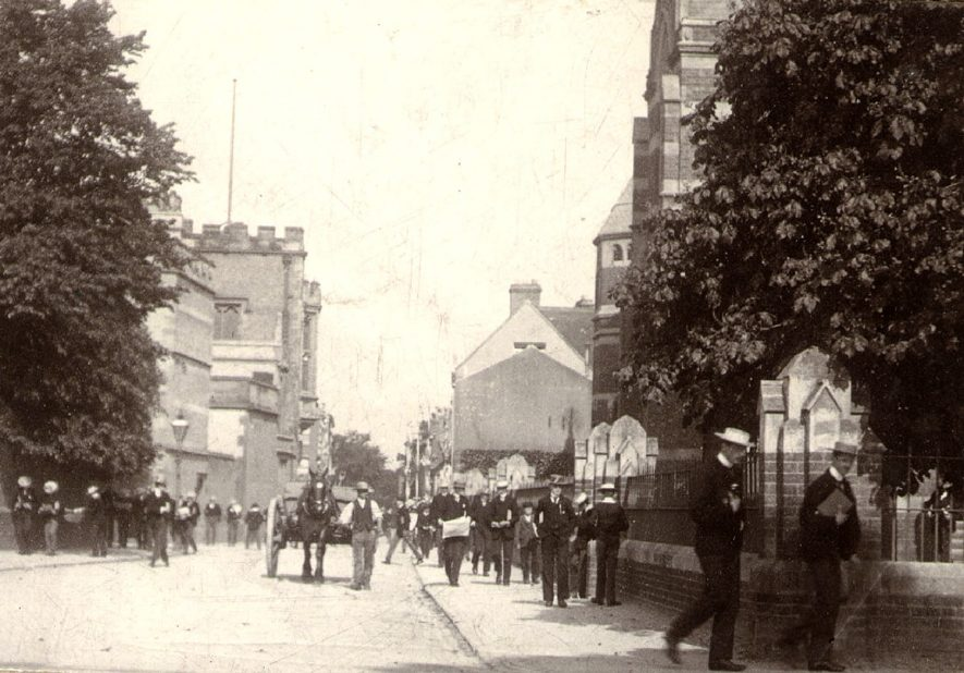 Lawrence Sheriff Street, showing School House on left, New Big School on right, Rugby.  Rugby school boys and man with horse and cart.  1890s |  IMAGE LOCATION: (Rugby Library)
