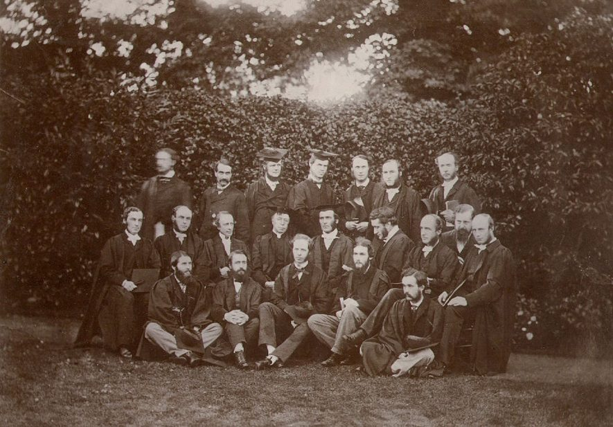 Rugby School assistant masters under Dr Temple in a group photograph in a garden setting.  Top row left-right: A.W. Potts, J.W.J. Vecqueray, C.E. Moberly, J.M. Wilson, H. Lee Warner, T.W. Jex-Blake, T.N. Hutchinson.  Middle row left-right: P. Bowden-Smith,  C.Elsee, L.F. Burrows, H.J. Buckoll, Dr Temple, C.T. Arnold, C.B. Hutchinson, H. Brandreth, J. Robertson.  Bottom row left-right: J.S. Phillpots, F.E. Kitchener, E.A. Scott, A. Sidgwick, E.F. Grefell.  1865 |  IMAGE LOCATION: (Rugby Library)