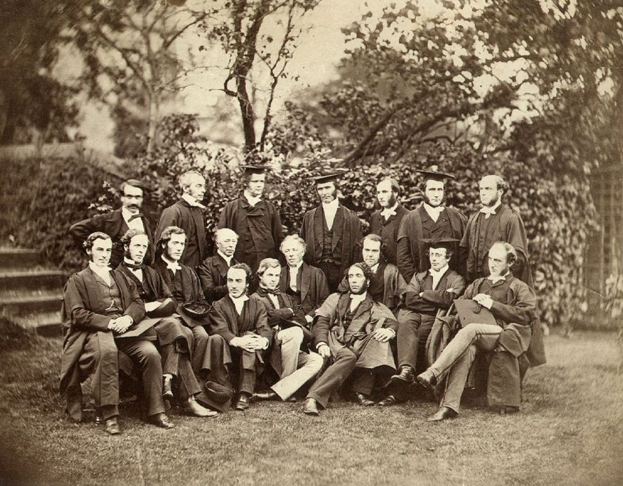 The Rev. F. Temple, Headmaster of Rugby School,  pictured with his assistant masters. Back row left to right - J.W.J. Vecqueray, Rev. C.T. Arnold, Rev. C.E. Moberley, Rev. F. Temple(headmaster), Rev. T.W. Jex-Blake, Rev. C.B. Hutchinson, Rev C. Elsee. Middle row left to right - Rev. P. Bowden-Smith, E.A. Scott, Rev. J. Percival, Rev. C. Anstey, unknown, Rev. R.B. Mayor, Rev. L.F. Burrows, A.W. Potts. Front row all unknown.  1861 |  IMAGE LOCATION: (Rugby Library) PEOPLE IN PHOTO: Vecqueray, J W J, Vecqueray as a surname, Temple, Revd F, Temple as a surname, Percival, Revd J, Percival as a surname, Moberley, Revd C E, Moberley as a surname, Mayor, Revd R B, Mayor as a surname, Jex-Blake, Revd T W, Jex-Blake as a surname, Hutchinson, Revd C B, Hutchinson as a surname, Elsee, Revd C, Elsee as a surname, Burrows, Revd L F, Burrows as a surname, Bowden-Smith, Revd P, Bowden-Smith as a surname, Arnold, Revd C T, Arnold as a surname, Anstey, Revd C, Anstey as a surname
