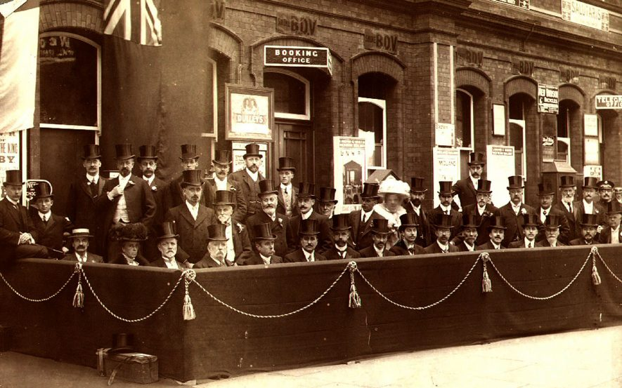 Rugby. Railway station platform.  Guardians &  representatives of the town awaiting the arrival of Edward VII for the opening of the Temple Speech room, 3rd July 1908. Top row left-right:  F.E. Hands, H.V. Wait, J.B. McDonald, William Clare Musgrave, J.M. Squires, W.J. Peddell, W.W. Webster, T. Spencer, T. Faulkner, Warren Hawkesley.  Middle row left-right :  G.W. Walton, J.W. Kenning, George Eaton, J.T. Fleet, Theo Foxon, J.W. Willard, Mrs Hadow,  E.F. Hadow, Rev. J.H. Lees, Rev. J. Linley, E.F. Barnwell, T.G. Hough, Ammon Bird, A. Almond, Ensign Skinner.  Bottom row left-right: C.F. Savage, Miss Alice McClure, J. Butcher, Richard Walker, A.G. Salter, T. Johnson, H. Lupton Reddish, J.W. Pendred, E.E. Crowhurst, Charles T. Tew, A. Daynes, Mr Sowerbutts, J.C. Harrison, Samuel Underwood, Frederick Stimpson, W.E. Robotham.   1909 |  IMAGE LOCATION: (Rugby Library) PEOPLE IN PHOTO: Willard, J W, Willard as a surname, Webster, W W, Webster as a surname, Walton, G W, Walton as a surname, Walker, Richard, Walker as a surname, Wait, H V, Wait as a surname, Underwood, Samuel, Underwood as a surname, Stimpson, Frederick, Stimpson as a surname, Squires, J M, Squires as a surname, Spencer, T, Spencer as a surname, Sowerbutts, Mr, Sowerbutts as a surname, Skinner, Ensign, Skinner as asurname, Savage, C F, Savage as surname, Salter, A G, Salter as a surname, Robotham, W E, Robotham as a surname, Reddish, H Lupton, Reddish as a surname, Peddell, W J, Peddell as a surname, Musgrave, William Clare, Musgrave as a surname, McDonald, J B, McDonald as a surname, McClure, Miss Alice, McClure as a surname, Lindley, Revd J, Lindley as a surname, Lees, Revd J H, Lees as a surname, Kenning, J W, Kenning as a surname, Hough, T.G., Hough as a surname, Hawkesley, Warren, Hawkesley as a surname, Harrison, J C, Harrison as a surname, Hands, F E, Hands as a surname, Hadow, Mrs, Hadow, E F, Hadow as a surname, Foxon, Theo, Foxon as a surname, Fleet, J T, Fleet as a surname, Faulkner, T, Faulkner as