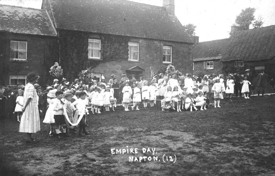'Empire Day', a large group of children outside house, some in fancy dress and with flags, flowers etc., with some adults.  1920s |  IMAGE LOCATION: (Warwickshire County Record Office)