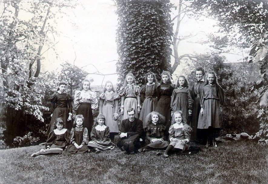 A group of girls with a parson, possibly Reverend Synge, Curate of St Andrews, Rugby.  1896 |  IMAGE LOCATION: (Rugby Library)