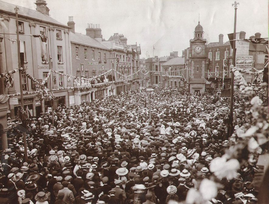 Crowds celebrating in Market Place, Rugby, for the coronation of King George V.  June 22nd 1911    IMAGE LOCATION: (Rugby Library)