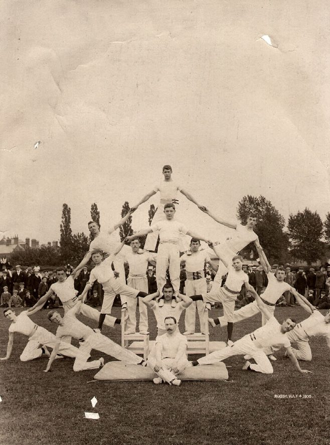 Rugby gymnastic club tableau in the Lawrence Sheriff School field on July 4th 1900.Back row from left to right - F.J. Gibson, S.G. Gibson, H. Hessian, T. Preston, W. Hessian, Yeomans, H. Castley. Second row - S. Orme, W. Moss, J. Smith, H. Gibbons, anon, O. Wright. Centre, kneeling - R.R. Tait, sitting - W.J. Steele. |  IMAGE LOCATION: (Rugby Library) PEOPLE IN PHOTO: Yeomans as a surname, Wright, O, Wright as a surname, Tait, R R, Tait as a surname, Steele, W J, Steele as a surname, Preston, T, Preston as a surname, Orme, S, Orme as a surname, Moss, W, Moss as a surname, Hessian, W, Hessian, H, Hessian as a surname, Gibson, F J, Gibson, S G, Gibson as a surname, Gibbons, H, Gibbons as a surname, Castley, H, Castley as asurname