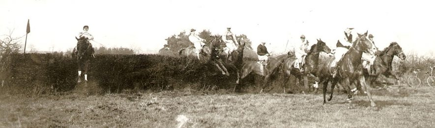 Horses and their jockeys jumping one of the fences at Rugby steeplechases.  March 28th 1913 |  IMAGE LOCATION: (Rugby Library)