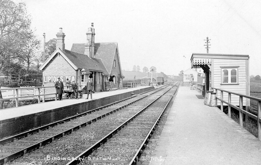 Birdingbury station showing the station master, a porter with a trolley on the platform and two milk churns.  1900s |  IMAGE LOCATION: (Warwickshire County Record Office)