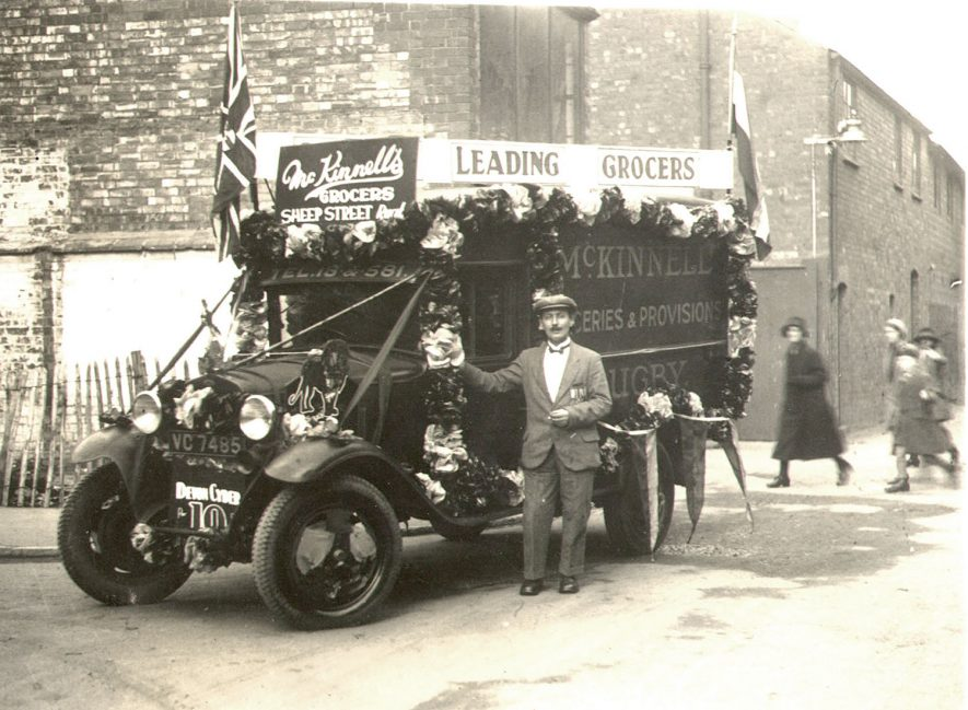 J. J. McKinnell's grocers delivery van decorated in Drury Lane, Rugby.  1920s |  IMAGE LOCATION: (Rugby Library)