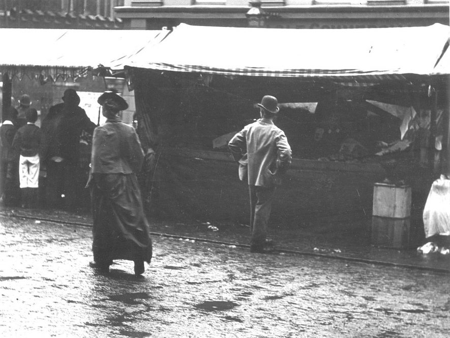 Stalls in Rugby Market Place.  Charter for weekly market granted 1255.  Market held here until 1953 when it relocated to Church Street on site previously occupied by Caldecott School.  1900s |  IMAGE LOCATION: (Rugby Library)