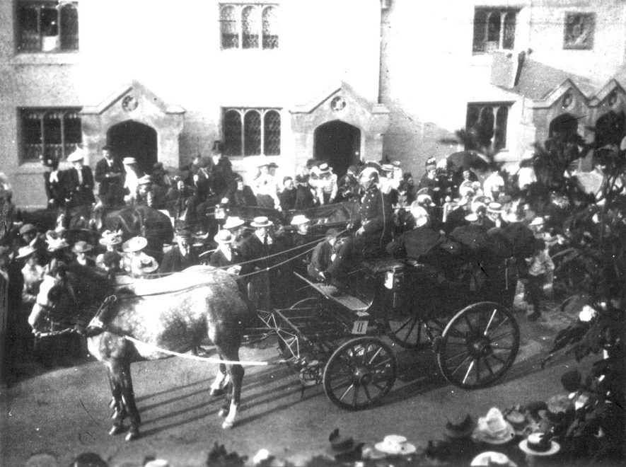 View of the Almshouses taken about 1900, with a parade of firemen? |  IMAGE LOCATION: (Rugby Library)