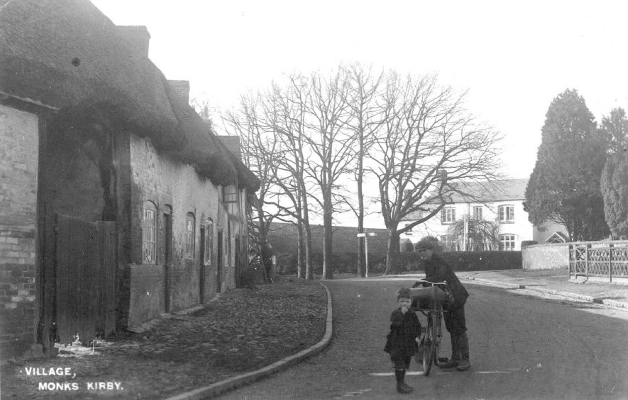 Man with bicycle and child standing in the road at Monks Kirby.  1920s    IMAGE LOCATION: (Warwickshire County Record Office)