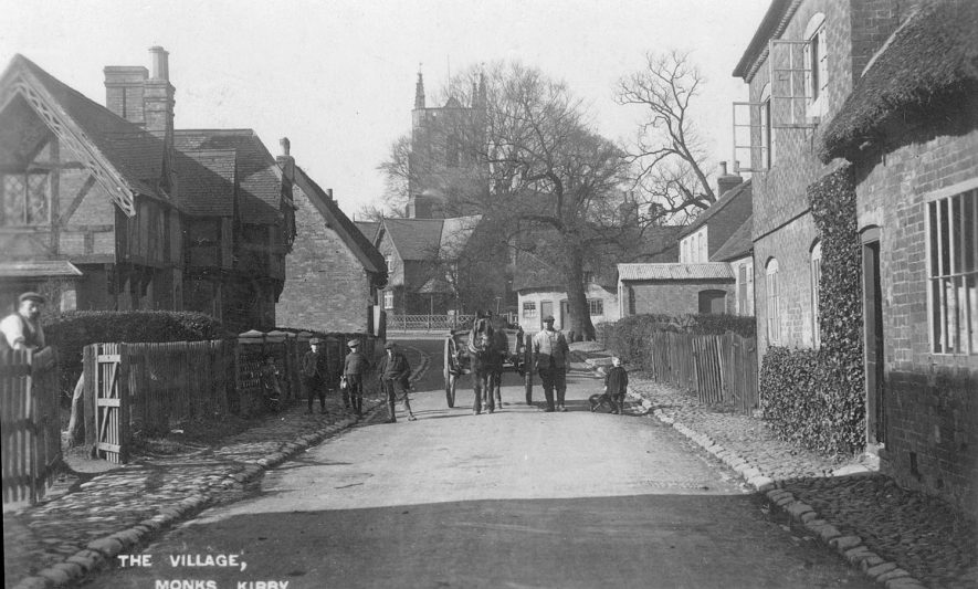 A village street in Monks Kirby with the church in the background. A horse and cart is seen approaching.  1920s    IMAGE LOCATION: (Warwickshire County Record Office)