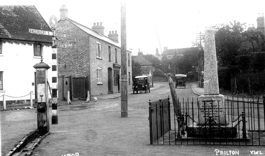 Village street in Pailton, with the war memorial and a water pump in the foreground and cottages and two cars in the background.  1930s |  IMAGE LOCATION: (Warwickshire County Record Office)