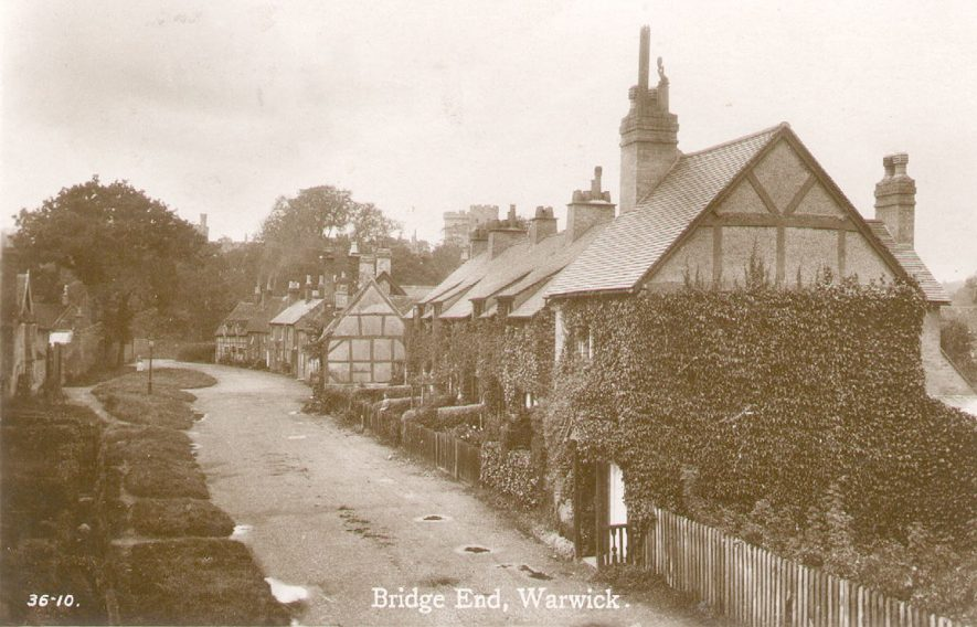 Cottages at Bridge End with the castle in the background.  1920s |  IMAGE LOCATION: (Warwickshire County Record Office)