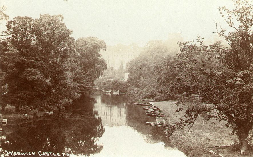 The River Avon and Warwick Castle from the bridge.  Pleasure boats are moored on the right hand side.  1900s |  IMAGE LOCATION: (Warwickshire County Record Office)