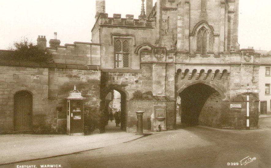 Eastgate, with telephone cabin, post box and drinking fountain under the walls, Warwick.  1930s    IMAGE LOCATION: (Warwickshire County Record Office)
