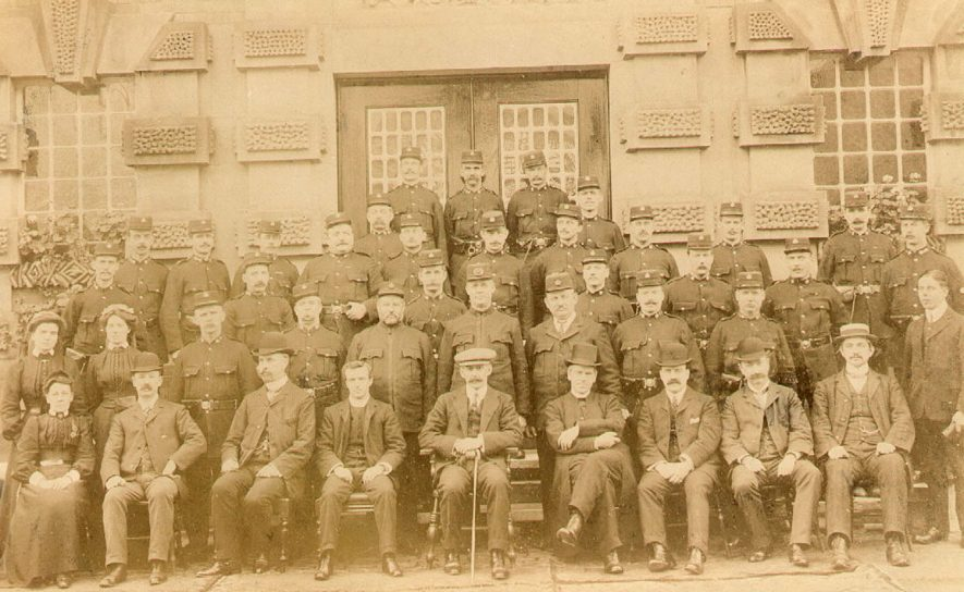 The Governor of Warwick prison, Mr D'Eath, seated in the centre, on his left, is the Chaplain to the prison, the Rev. Hall, who died in 1912. The staff at His Majesty's Prison, Warwick on 26th November 1907, the last year in which Captain D'Eath was governer. They are from left to right, starting on the back row: Williams, Light and Northwood. Next row: Holmes and ? Machise. On the third row: Walters, Tomlinson, Collins, Fitzgerald, Deavall, Page, Lea, Gilkes, Clearn and Heard. Next row: Hides, Corbridge, Russell, Parsons, Tyler, Matthews and Boyden. Next row: Miss Symes and Miss Dempster, Carr, Denton, Stevenson, Martin, Heales, Holland (cook) Palmer and C.Winston (organist). On the front row are: Miss Madeley (matron) E.Arbury,(clerk) M.G.H.Master (storekeeper) Reverend A.M.Stephens (chaplain) Captain R.H.D'Eath (governor) Reverend A.Hall (Roman Catholic chaplain) Dr H. Tibbits (medical officer) P.Piggott (clerk) and E.J.Nickisson (school master). c.1910 |  IMAGE LOCATION: (Warwickshire County Record Office) IMAGE DATE: (c.1910) PEOPLE IN PHOTO: Hall, Reverend, Hall as a surname, D'Eath, Mr, D'Eath as a surname