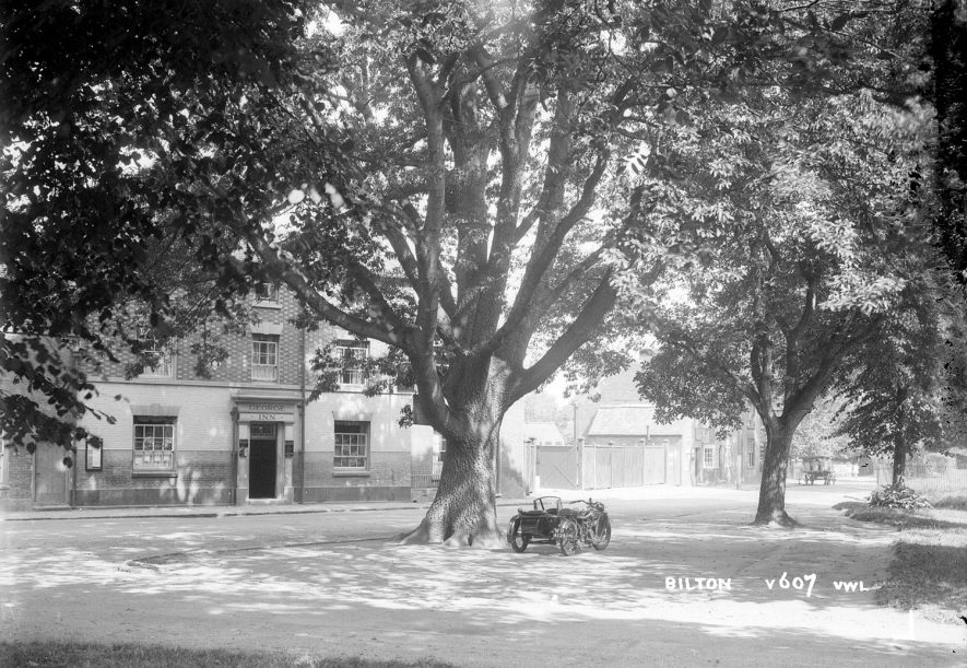 The George Inn from The Green, Bilton, with a motorcycle and sidecar standing under a tree.  1930s |  IMAGE LOCATION: (Warwickshire County Record Office)