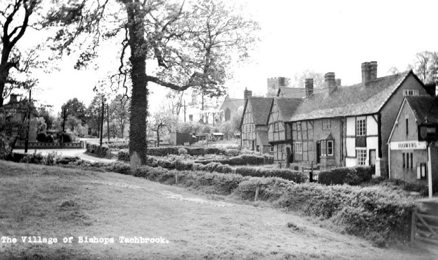 Scene of part of Bishops Tachbrook village showing timber framed cottages with church in the background.  1950s |  IMAGE LOCATION: (Warwickshire County Record Office)