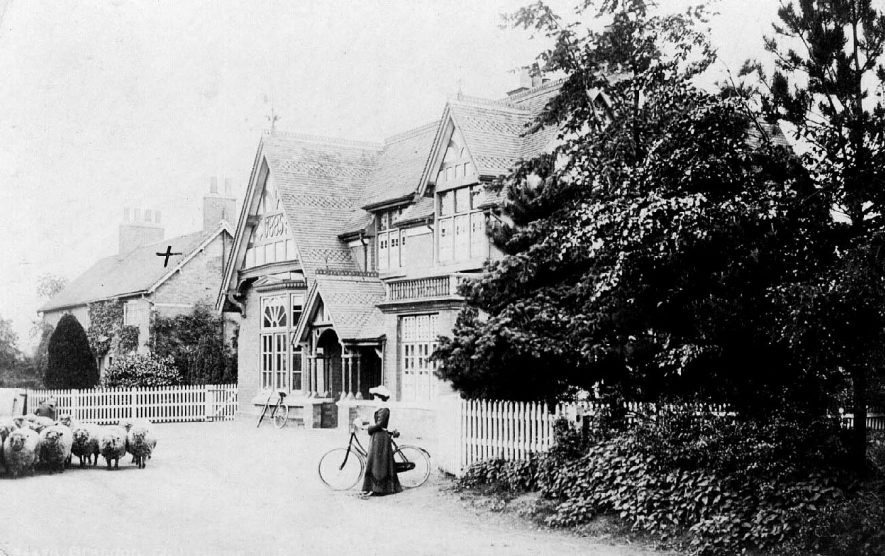 Front exterior of Brandon Working Men's Club, showing lady with bicycle and flock of sheep.  1900s |  IMAGE LOCATION: (Warwickshire County Record Office)