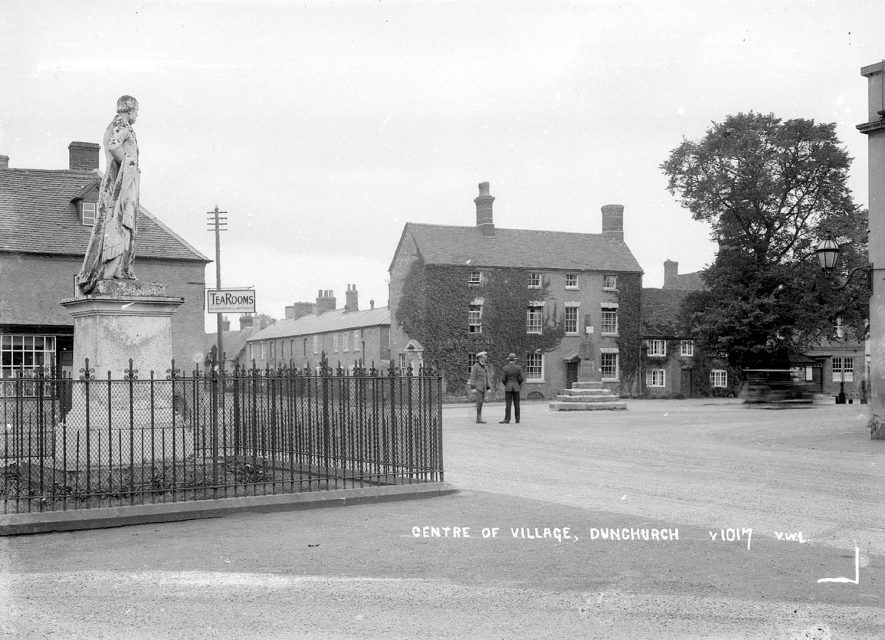 The Square, Dunchurch. 1950s[This photograph is taken by the almshouses in Dunchurch. There is a slip road from the Rugby Road to the Daventry Road, this leads to the church and the war memorial and provides access to the almshouses. In the background you can see the back of Lord John Scott's statue, the side of The Dun Cow and the village cross.] |  IMAGE LOCATION: (Warwickshire County Record Office)