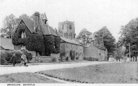 A street in Brinklow, showing school buildings, cottages, church tower, men and bicycles.  1920s |  IMAGE LOCATION: (Warwickshire County Record Office)
