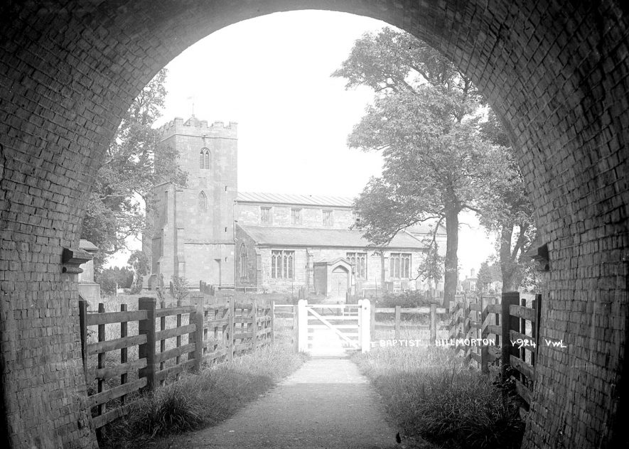 The church of St John the Baptist, Hillmorton, seen through a brick archway.  1930s |  IMAGE LOCATION: (Warwickshire County Record Office)