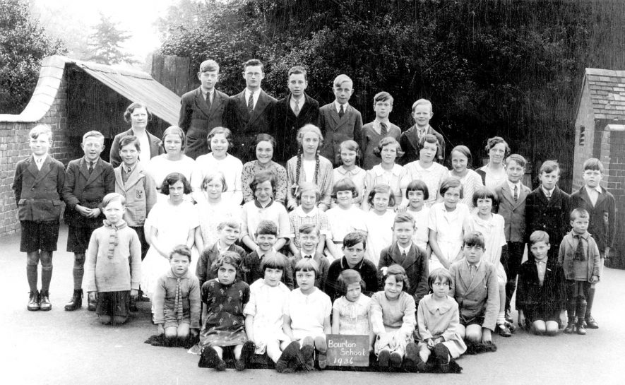 Photograph of children and teachers at Bourton on Dunsmore C of E junior and infant school 1936.   Showing  Miss Hales who was a pupil at the school, a pupil teacher, a teacher and finally a manager.  She died in February 1974, aged 91 or 92 |  IMAGE LOCATION: (Warwickshire County Record Office) PEOPLE IN PHOTO: Hales, Miss, Hales as a surname