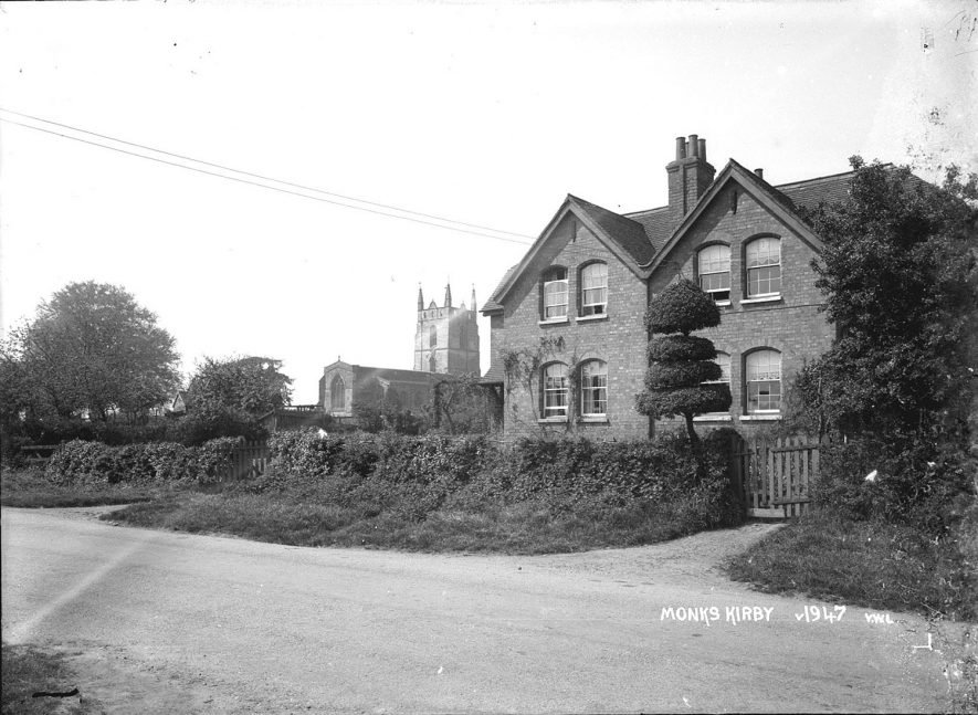 A large detached house with the church in the background, Monks Kirby.  1950s |  IMAGE LOCATION: (Warwickshire County Record Office)