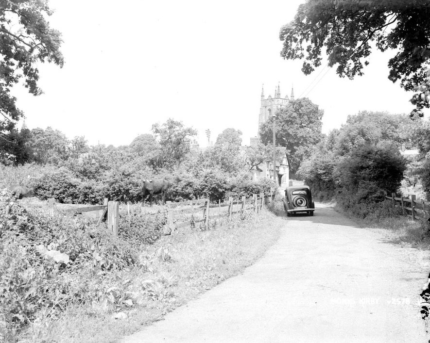A country lane in Monks Kirby with the church in the background.  1950s    IMAGE LOCATION: (Warwickshire County Record Office)