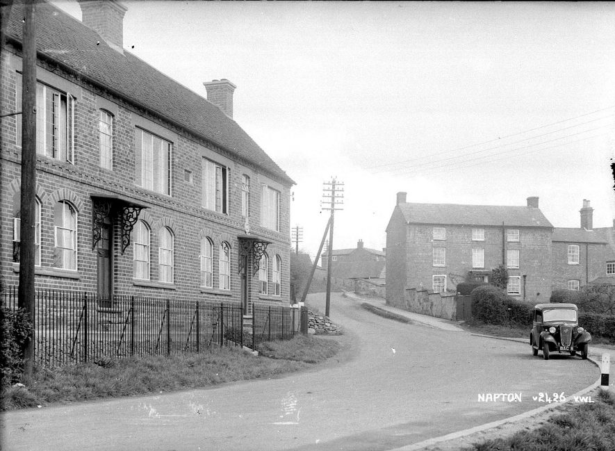 Terraced houses and car in Napton on the Hill. Houses built by Mr Percy Cox of Long Itchington.  Arched windows on ground floor were taken from demolished Warwick Gaol.  1950s