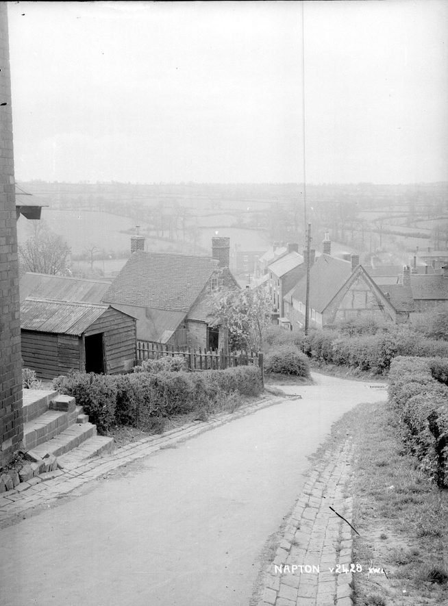 A view looking down over Napton on the Hill.  1950s  [View looking down Church Hill. The house in the centre is The Old Bakery Cottage, one of the oldest properties in the Village.] |  IMAGE LOCATION: (Warwickshire County Record Office)