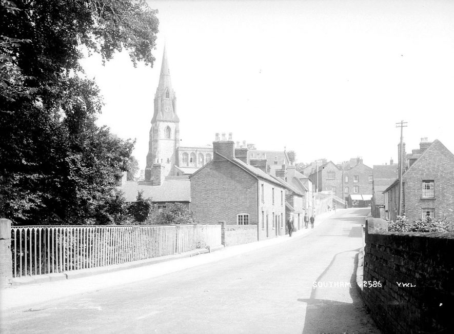 A street in Southam with terraced housing and the parish church in the distance.  1952 |  IMAGE LOCATION: (Warwickshire County Record Office)