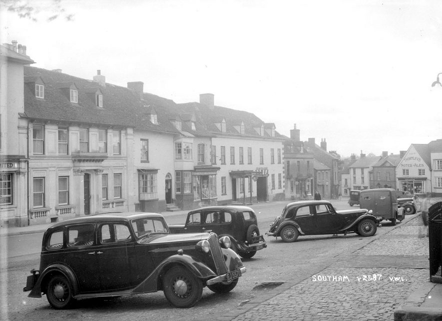 A street in Southam with shops and parked cars.  1952 |  IMAGE LOCATION: (Warwickshire County Record Office)