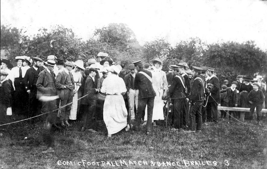 Comic football match and dance. Group of people, including men, women, children and bandsmen. No obvious sign of either football match or dancing.  Lower Brailes.  1910s |  IMAGE LOCATION: (Warwickshire County Record Office)
