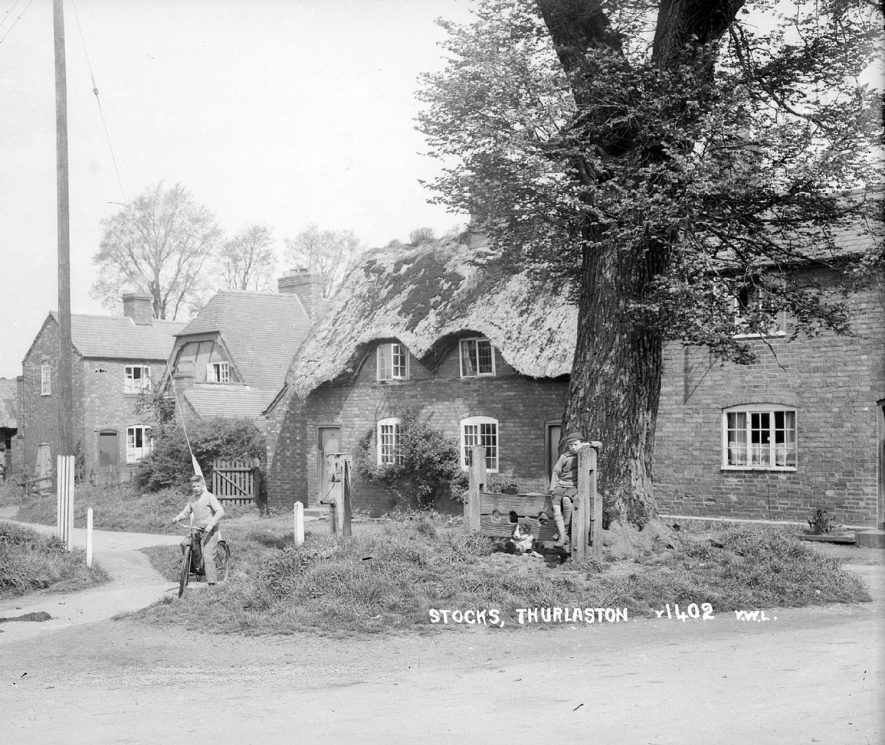 Thatched cottages in Thurlaston, with a water pump and stocks in front.  1930s |  IMAGE LOCATION: (Warwickshire County Record Office)