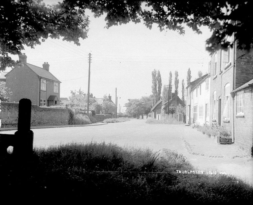 Thurlaston village with the edge of the stocks showing in the foreground.  1930s |  IMAGE LOCATION: (Warwickshire County Record Office)