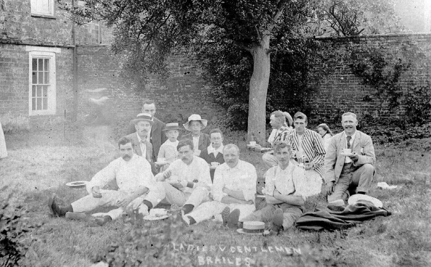 Group of cricket players sitting on grass either before or after Ladies v Gentlemens match, Lower Brailes.  1908 |  IMAGE LOCATION: (Warwickshire County Record Office)