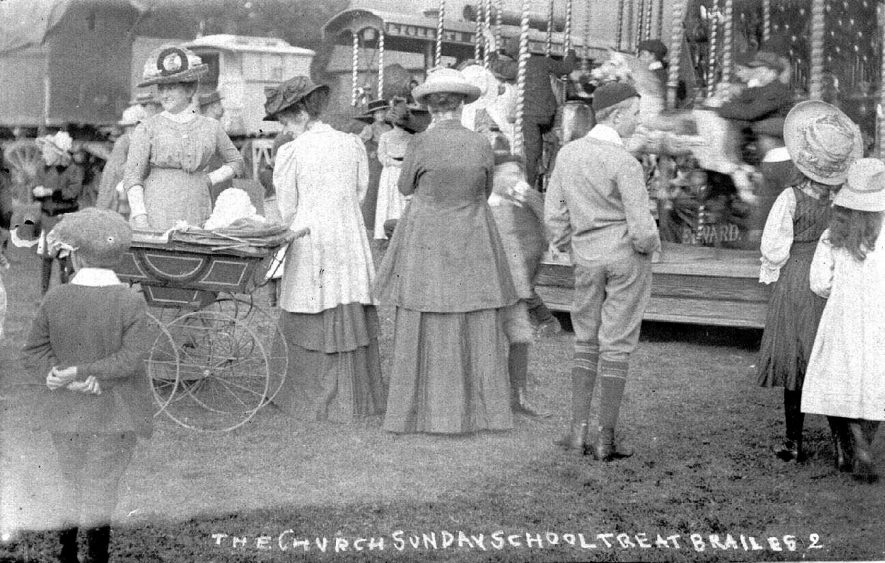 Church Sunday School treat, showing family groups with perambulator and fairground equipment in use, Lower Brailes.  1900s |  IMAGE LOCATION: (Warwickshire County Record Office)